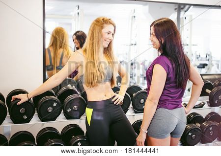 Girl In A Bright White Gym. Two Young Sports Women Are Chatting Cutely Near Sports Equipment About T
