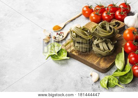 Raw Paste Of Tagliatelle With Spinach And Ingredients For Cooking (cherry Tomatoes, Spices, Garlic,