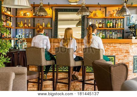 Three beautiful young girls in uniform sit on chairs in restaurant back view