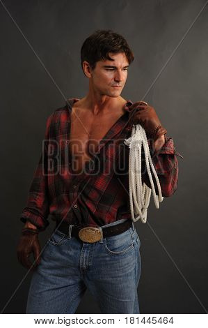 The hot cowboy is holding his rope.