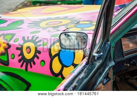 Closeup image of side mirror and door of obsolete bright colorful car at festival