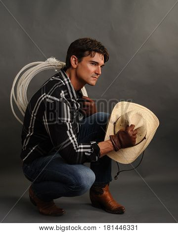 The deviant cowboy is crouched down relaxing.