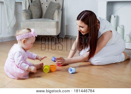 happy young mother and baby playing at home
