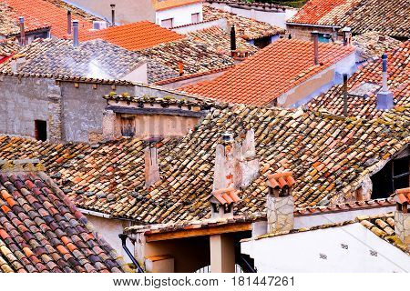 the roofs of a number of spanish houses in a village with pantiles and chimneys