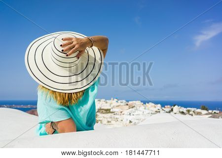 Elegant lady on holidays in Santorini Greece enjoying the view on the rooftop