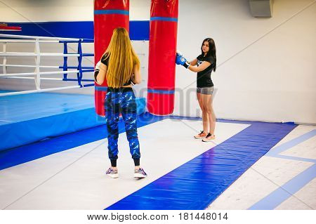 Young Woman Exercising In The Gym On Punching Bag. Two Girls Are Engaged In Martial Arts Training, P