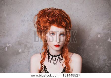 A woman with hairdo and red hair in a nightgown. Red-haired girl with hairdo and pale skin and blue eyes with bright unusual appearance with choker around her neck on a background of gray wall. French courtesan with hairdo. Copyspace