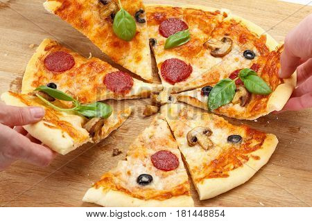 People take pizza slices with cheese mushrooms salami and crumbs on a rustic wooden table close-up.