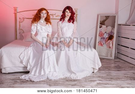 Two vintage beautiful girls with red hair in a beautiful vintage white wedding Victorian dresses. Female style. The fragile vintage girl. Thin waist. Two vintage women sitting in the bedroom on a white vintage bed