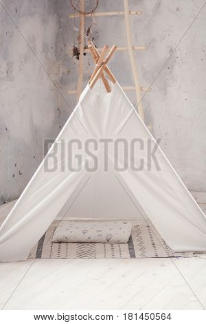 Childen's room corner with a beautifully decorated play tipi tent and a round grey carpet.