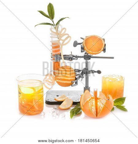 Orange with a leaf peeled in a spiral skin in a laboratory for the production of bio juice test tubes laboratory tripod clamps terminal clips white background original concept