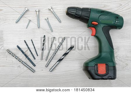 A green electric drill, several twisted drill bits and bolts placed on a white wood background. Hobby and DIY. Construction and building. Maintenance works.