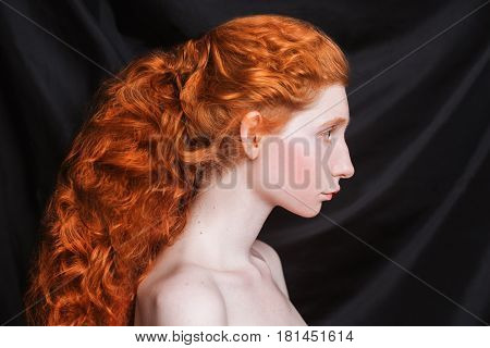 Retro woman with long curly red hair gathered in ponytail on black background. Red-haired retro girl with pale skin blue eyes unusual appearance without makeup. Natural beauty. Retro girl from the era of renaissance. Retro model