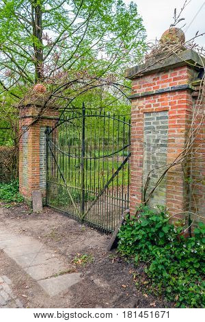Weathered black painted iron gate between pillars built with red and grey bricks.