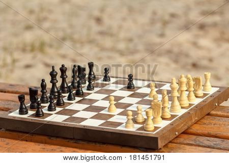 Chess board with chess pieces on wooden bench. Outdoors chess game with wooden chess pieces in sunny day