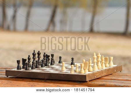 Chess board with chess pieces on wooden bench. Outdoors chess game