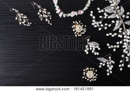 Jewelery for hair and white earrings made of beads on a dark background. Women's jewelry. Jewelery on the table. Jewelry on a dark background. Jewelry from beads.