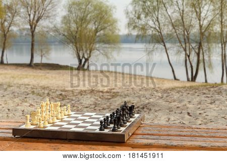 Chess board with chess pieces on wooden bench with river embankment background. Outdoors chess game with wooden chess pieces