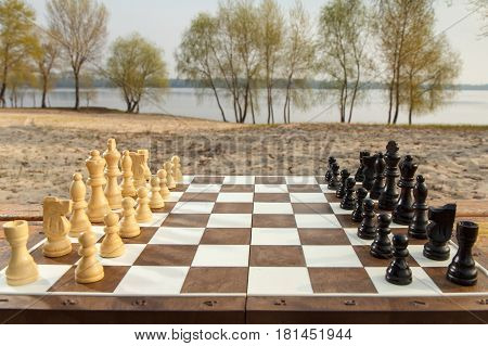 Chess board with chess pieces on river embankment background. Outdoors chess game with wooden chess pieces