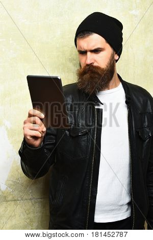 Bearded man long beard. Brutal caucasian serious unshaven hipster holding tablet in black leather jacket on battered texture wall background