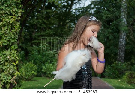Little princess girl eating sweet cotton candy