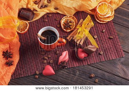 Chocolates in the shape of heart and lips orange cup of black coffee roasted coffee beans dried lemon slices with spices cinnamon and anise on dark background. Chocolate confectionery concept