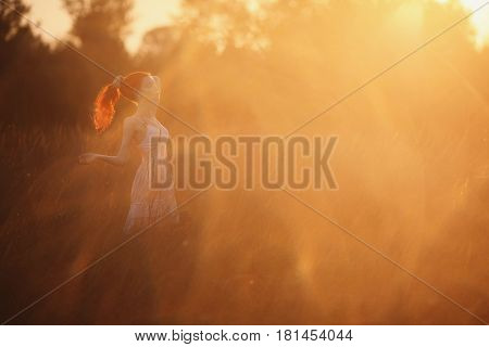 A woman with red curly hair in white sundress on background of dawn. Early morning. Meet the dawn in the morning. Morning in nature. The sun rises in the morning. Girl on the background of the morning nature. Red-haired girl with pale skin bright unusual