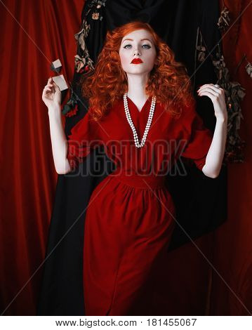 A thin woman with red hair in a red fitting dress. Red-haired thin girl with pale skin and blue eyes with a bright unusual appearance with beads around her neck. Noir thin woman. Thin waist