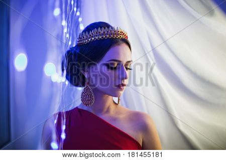 Eastern girl brunette in a red dress with beautiful hairstyle earrings of beads and a eastern crown on her head and bright makeup. Female eastern style. Mysterious eastern woman. Blue light. Eastern model