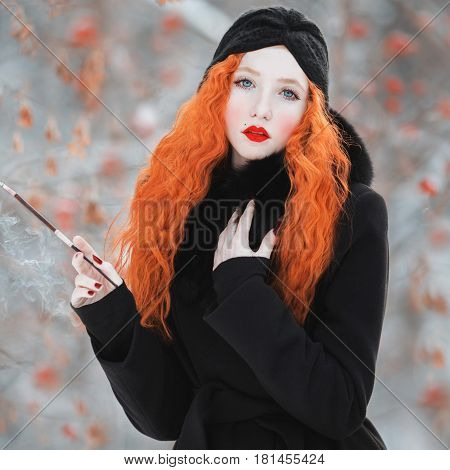 A woman with red hair in a black coat on background of a winter forest with a mouthpiece in hand. Red-haired girl with bright appearance with a turban on her head with a cigarette. Smoking aesthetics
