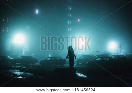 Mysterious lonely man. Mysterious city at night in dense fog. Thick smog on a dark mysterious street. Beautiful mixed lighting from windows. Mysterious silhouettes of people and trees. Pillars at road