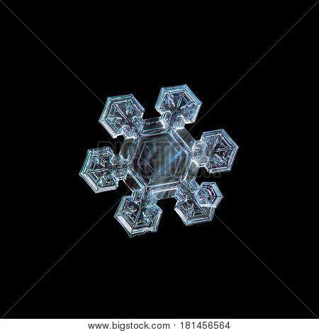 Macro photo of real snowflake: medium size snow crystal of star plate type with simple shape, six short and broad arms with complex inner details, and large central hexagon with simple pattern inside. Snowflake isolated on pure black background.