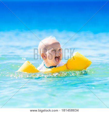 Baby Swimming In Ocean Water On Tropical Beach