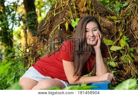 Smiling Woman Seated And Leaning On A Bench