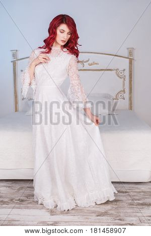 Beautiful slim girl with red hair and natural make-up and pale skin. A slim woman in a white dress renaissance. Slim model posing in studio. The unusual appearance. The slim bride in the bedroom
