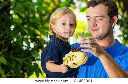 Son On His Father's Lap Holding A Dinosaur Toy