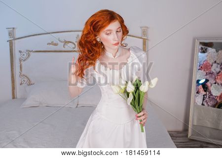 Woman with long red curly hair in white vintage wedding dress with white pearl earrings on ears with flowers. Red-haired girl with pale skin blue eyes unusual appearance in the bedroom with white tulips flowers in hand. Beautiful flowers. A model with flo