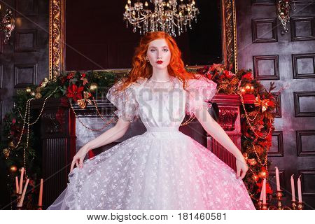 Luxury woman with long red curly hair in a white luxury vintage wedding dress with white pearl luxury earrings on her ears. Red-haired luxury girl with pale skin a bright unusual appearance on the background of luxury fireplace. Luxury model