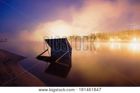Fog over the river. The beautiful night scenery. Slow shutter speed. Spectacular clear starry sky. Scenic view. Beautiful landscape. Night landscape. Misty landscape. City landscape. Landscape with a view of the river. Morning landscape. Light from the ci