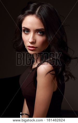 Beautiful Young Makeup Female Model In Brown Dress And Curly Hairstyle Looking Emotional On Dark Sha
