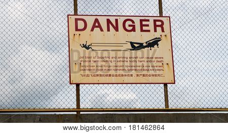Sign warning of the dangers of jet wash from aircraft landing and taking off from a nearby runway