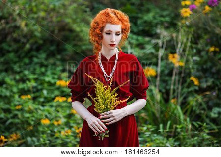 A woman with red hair and a red slinky dress with a bouquet of yellow flowers in hand. Red-haired girl with pale skin blue eyes and bright unusual appearance with a necklace of beads around her neck. Yellow flowers in a hand. Yellow background. Yellow bou