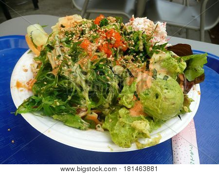 Hawaiian poki bowl with sciip of avocado in front on blue tray at table