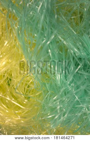 This is a photograph of Green and Yellow shredded plastic fake Easter grass background