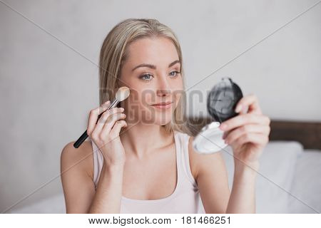 Young woman sitting on bed doing makeup