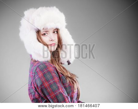 Winter fashion. Close up young woman wearing fashionable wintertime clothes white fur cap studio shot on gray background