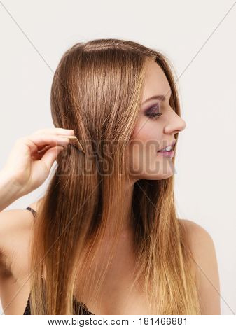Woman Combing Her Long Hair With Wooden Comb