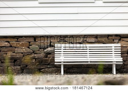 Place to relax concept. Symmetrical one white bench in front of traditional scandinavian light wooden house with windows.