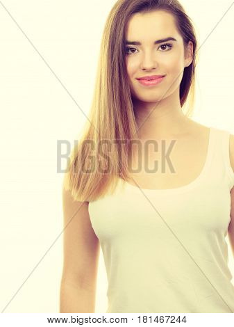 Teenage beauty concept. Portrait of young teenager woman with long brown having happy face expression wearing white tank top.