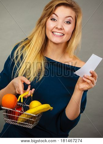 Happy woman holding shopping basket with fruits looking at bill receipt enjoying low prices.